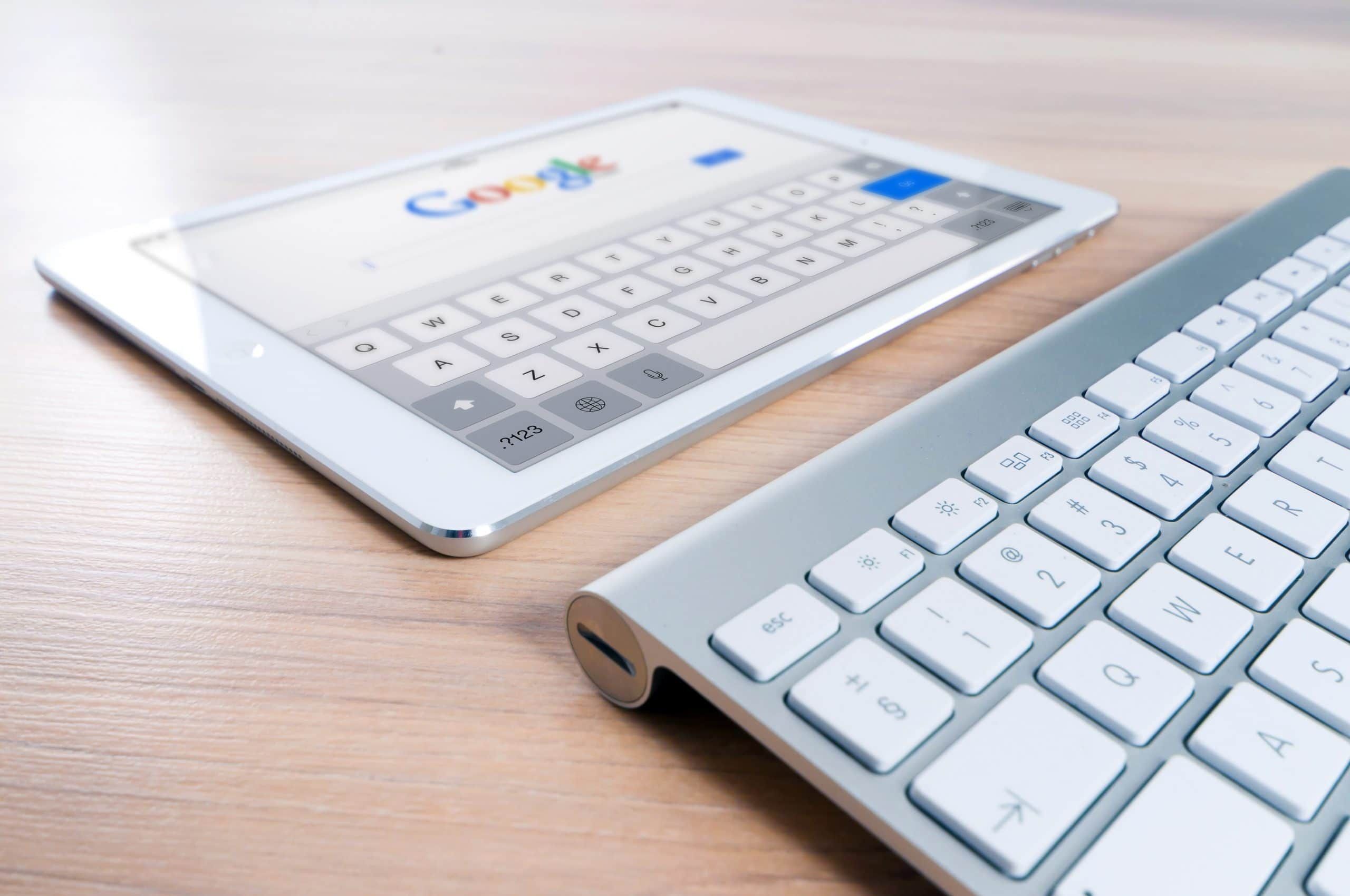 Tablet, open to Google home page, in front of a keyboard on a wood desk.