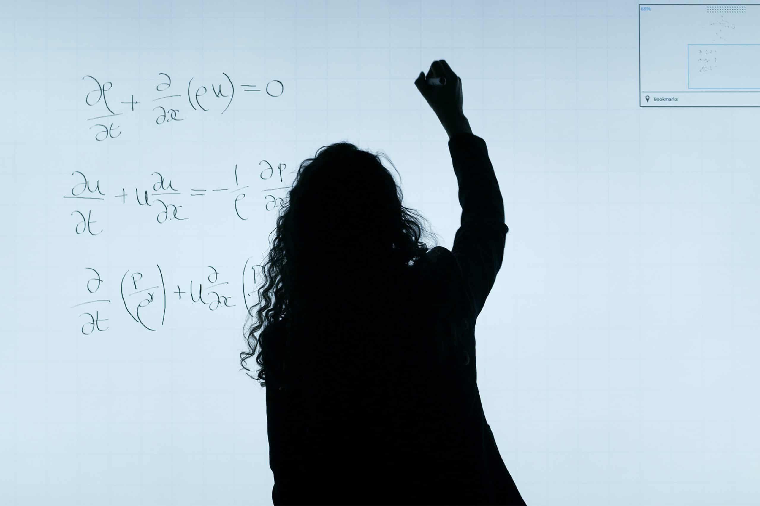 Silhouette of a woman writing on a whiteboard.
